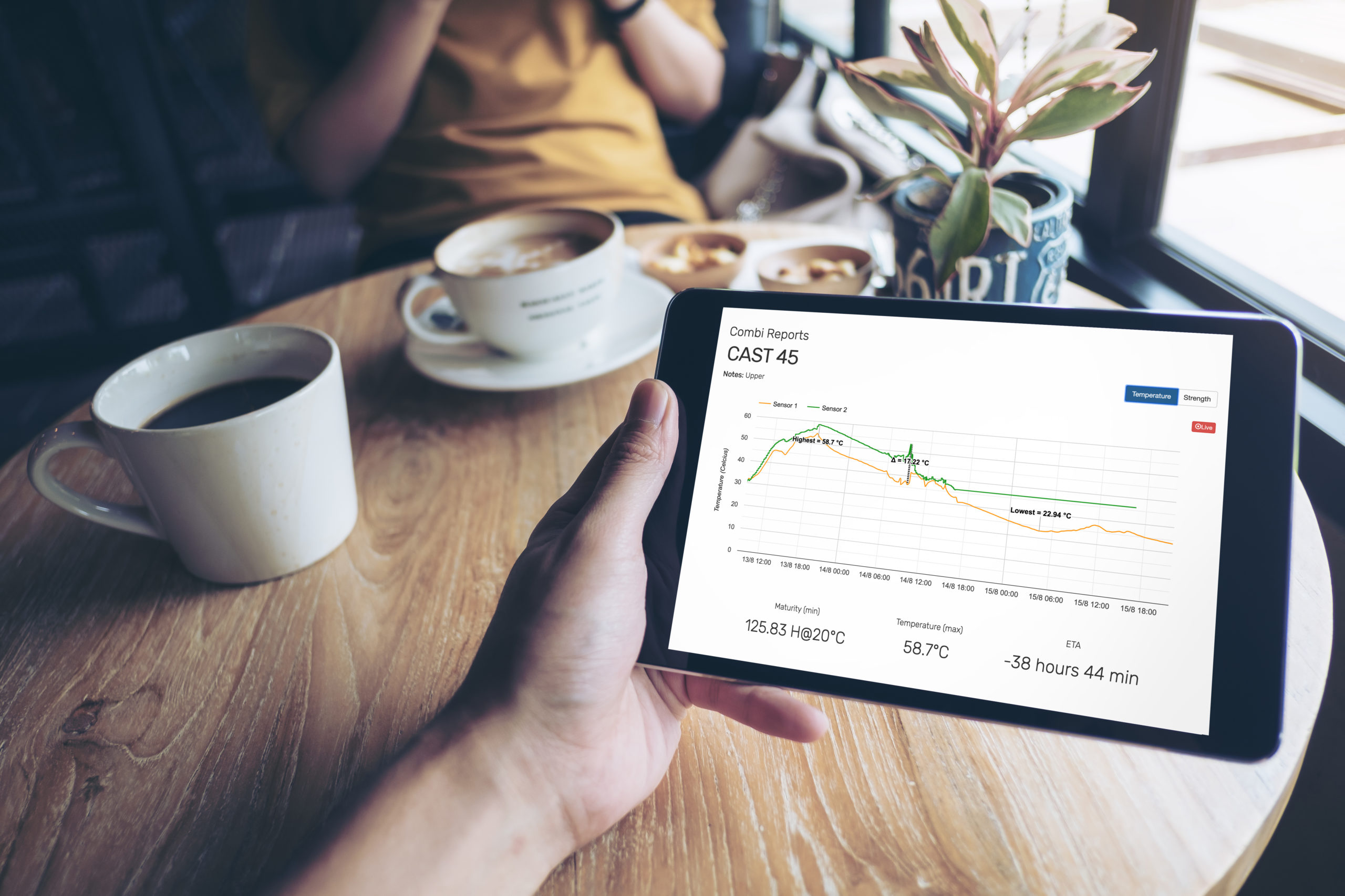 A coffee cup on a light-brown wooden table rests in the background as a builder holds a tablet in their left hand looking at sensor data in the foreground.